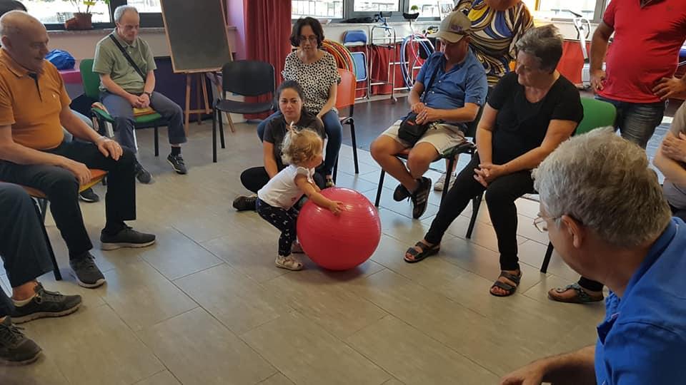 bimba che gioca con la palla insieme a persone con demenze, associazione ragi